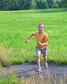 Small boy running on green meadow — Stock Photo