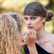 Makeup master applying lipstick with brush — Stock Photo