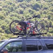 Three bicycles on the top of car near forest - Stock Photo