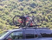 Three bicycles on the top of car near forest — Stock Photo