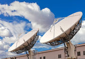 Satellite TV antenna on blue sky and clouds background — Stock Photo