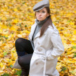 Beautiful woman in cap and white coat — Stock Photo