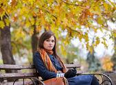 Bankta oturan genç kadın — Stok fotoğraf