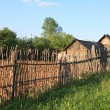 Stock Photo: Old wooden fence near farmhouse