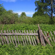 Old wooden fence near farmhouse — Stock Photo