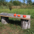 Red tomatoes on wooden bench — Stock Photo