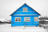 Blue house amongst white snow — Stock Photo