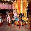 Royalty-Free Stock Photo: Child rides a carousel in the evening park.