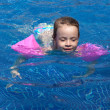 Stock Photo: Joyful little girl swimming in the pool.