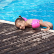 Joyful little girl on the side of the pool. — Stockfoto