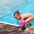 Joyful little girl on the side of the pool. — Стоковая фотография