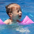 Upset little girl swimming in the pool. — Стоковая фотография