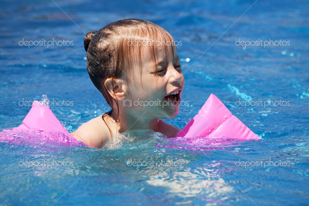 Upset little girl swimming in the pool.  Stock Photo #7154213