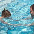 Dad teaches his daughter to swim in the pool. - Stock Photo
