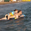 Man with daughter riding on an inflatable raft in the sea. — 图库照片