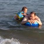 海のゴムボートに乗っての娘を持つ男 — ストック写真