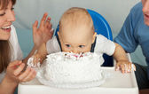 Kid eats cake. Family celebrates the first birthday of his son. — Stock Photo