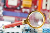 Magnifying glass and circuit board — Stock Photo