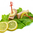 Sliced ham on leaves of salad with lemon — Stock Photo #7511473