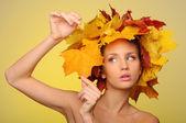 Mooie vrouw met Herfstbladeren op geel — Stockfoto
