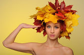 Beautiful woman with autumn leaves saluting — Stock Photo