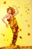 Woman in dress of leaves and defoliation — Stock Photo