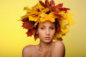 Beautiful woman with autumn leaves on yellow — Stock Photo