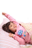 Little girl stretching in bed — Stock Photo