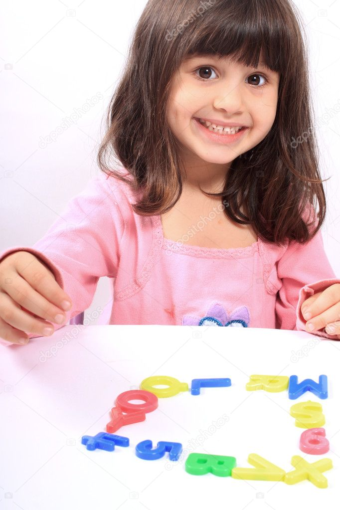 Young little preschool girl with funny expression playing with letters and numbers  Stock Photo #6828384