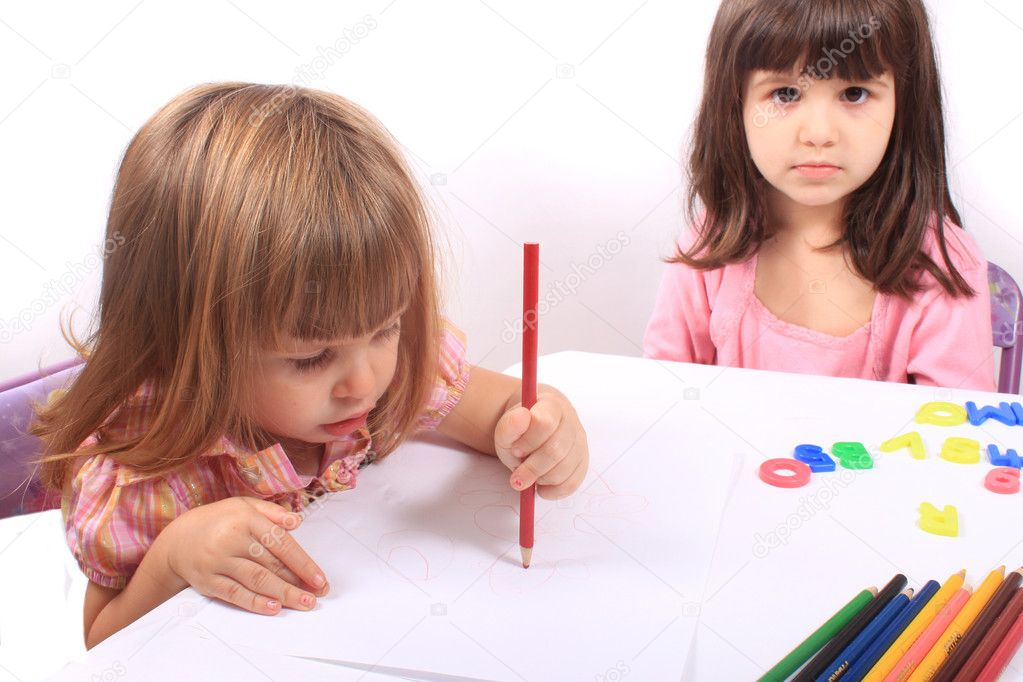 Two little preschool girls, one drawing with pencil the other playing with letters — Stock Photo #6851801