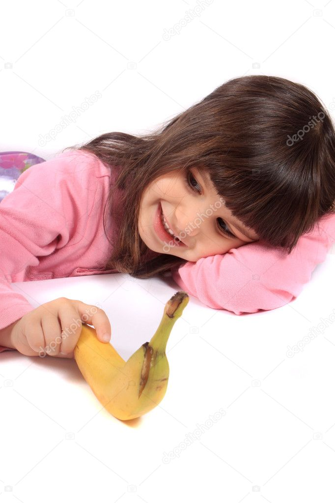 Young little girl laying on white background holding a banana and smiling — Stock Photo #6925232