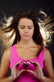 Beautiful young female holding a heart — Stock Photo