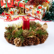 Christmas fir-cone wreath with candle and presents — Stock Photo
