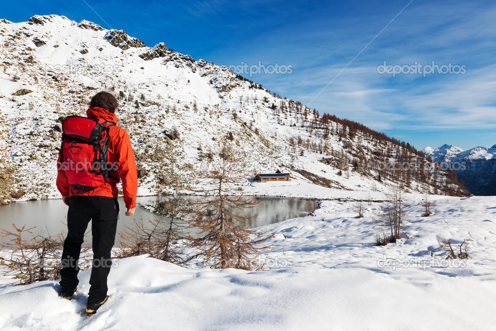 One man young male hiker stands in front of a alpine lake looking to the snowy landscape, rear view. Red jacket, black pants. Large copy-space at top-right. Buf — Stock Photo #7703270