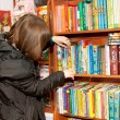 Young womstands in front of bookshelves and chooses book — Stock Photo #7901988