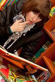 Szczęśliwa młoda kobieta czytać książki przed regały — Zdjęcie stockowe