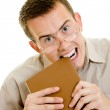 The man in glasses eats book. — Stock Photo
