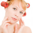 Woman in curlers on a white background. — Stock Photo