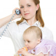 Businesswoman with a baby in her arms on the phone. — Stock Photo