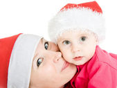 Happy Christmas mother kissing daughter on a white background. — Stock Photo
