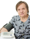 An elderly woman with a sphygmomanometer on a white background. — Stock Photo