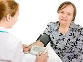 Läkaren och en äldre kvinna med en blodtrycksmätare på en vit ba — Stockfoto