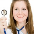 Royalty-Free Stock Photo: Female doctor smiling with stethoscope in hand on white background.