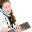 Female doctor talking on the phone and writing on the document plate on a w - Foto Stock