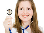Female doctor smiling with stethoscope in hand on white background. — Stock Photo