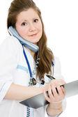 Kvinnliga läkare talar i telefon och skriva på dokument plattan på en w — Stockfoto