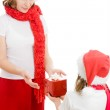 Daughter gives her mother a Christmas gift on white background. — Stock Photo