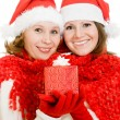 Two woman with Christmas presents on a white background. — Stock Photo