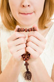 A girl holds a rosary in his hands on a white background. — Stock Photo