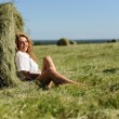 Woman sit near haystack — Stock Photo